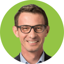 A white man smiling in a green circle background