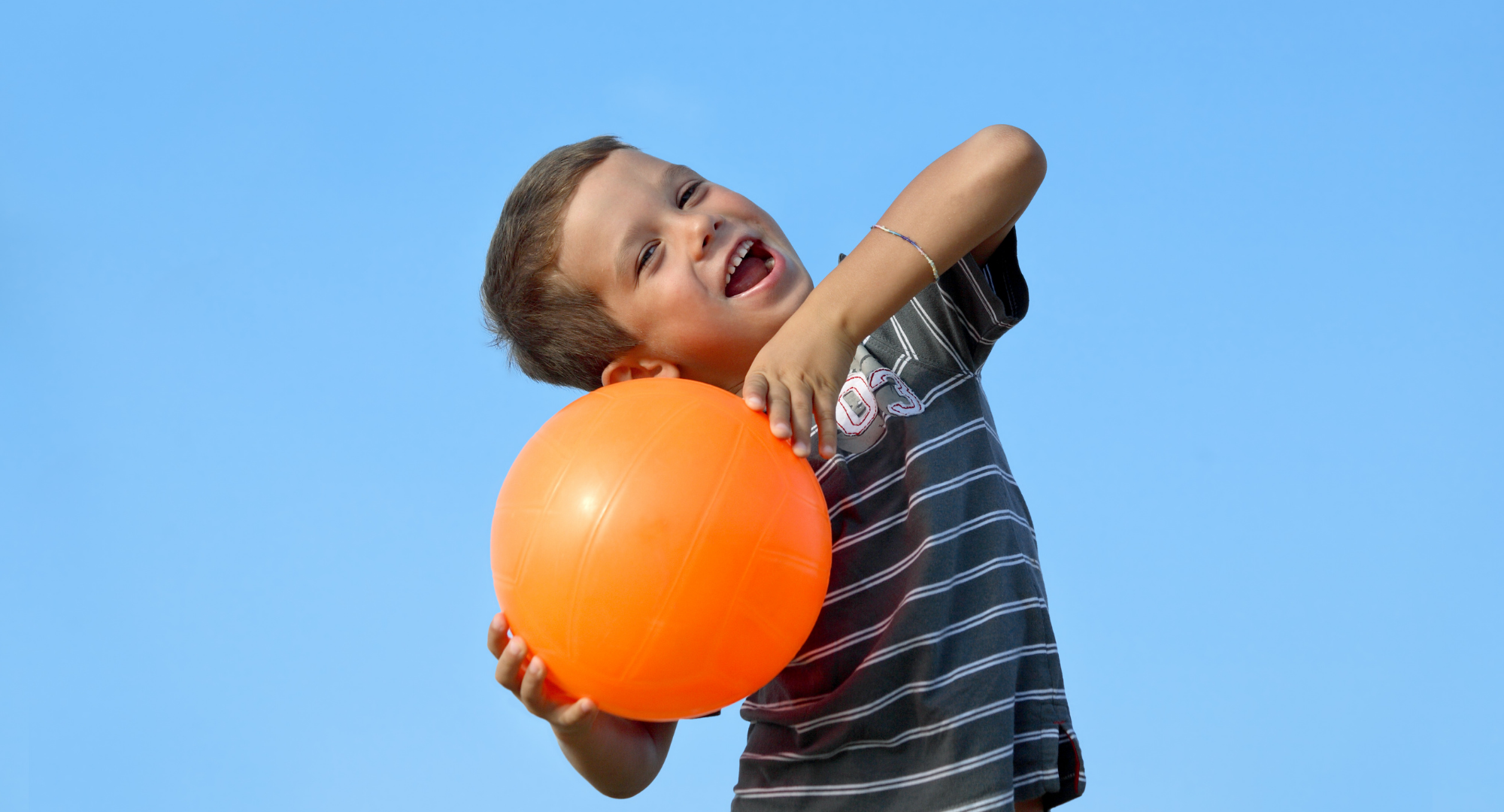 A boy smiling with an orange ball