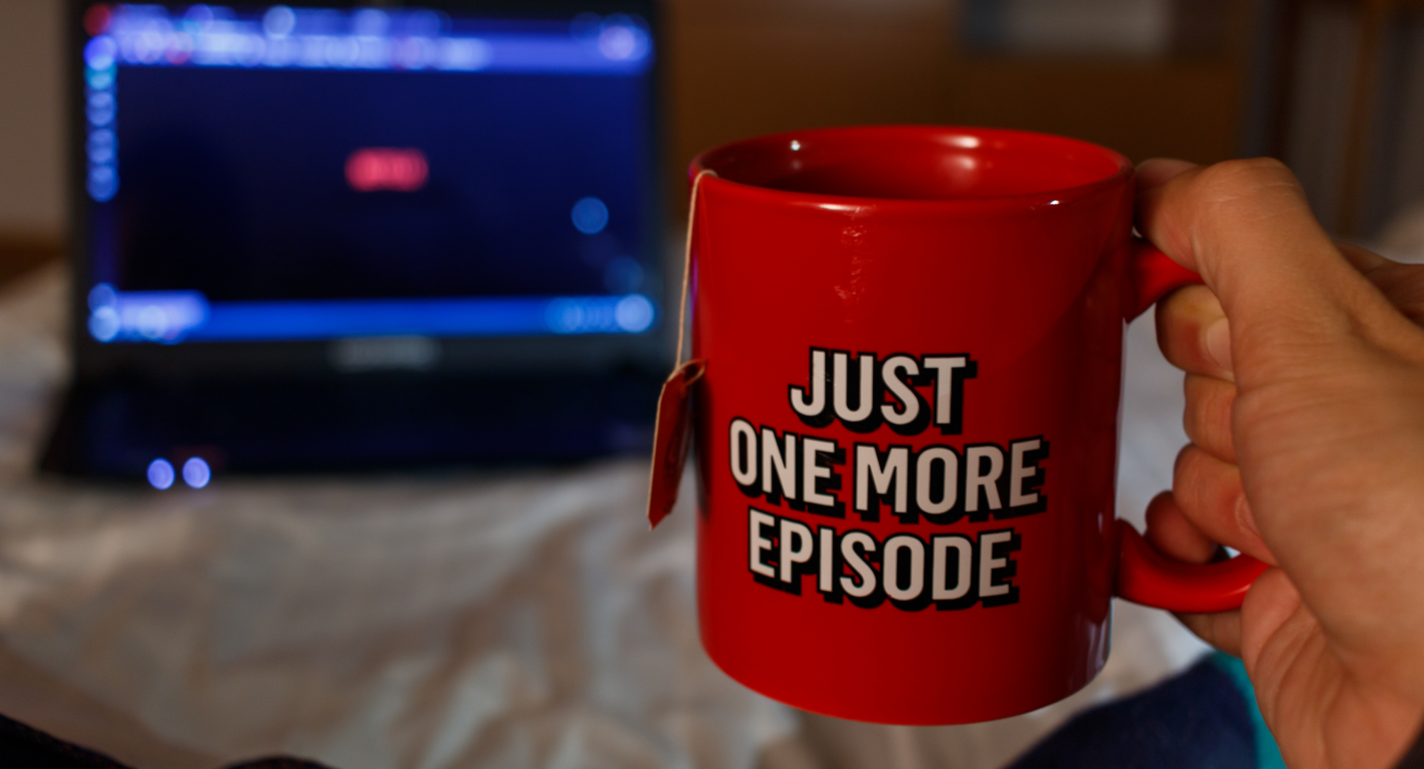 A person holding a mug that saying 'Just one more episode'