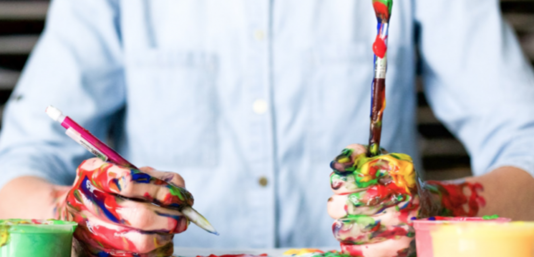 A man covered in paint holding a pencil in one hand and a paint brush in the other
