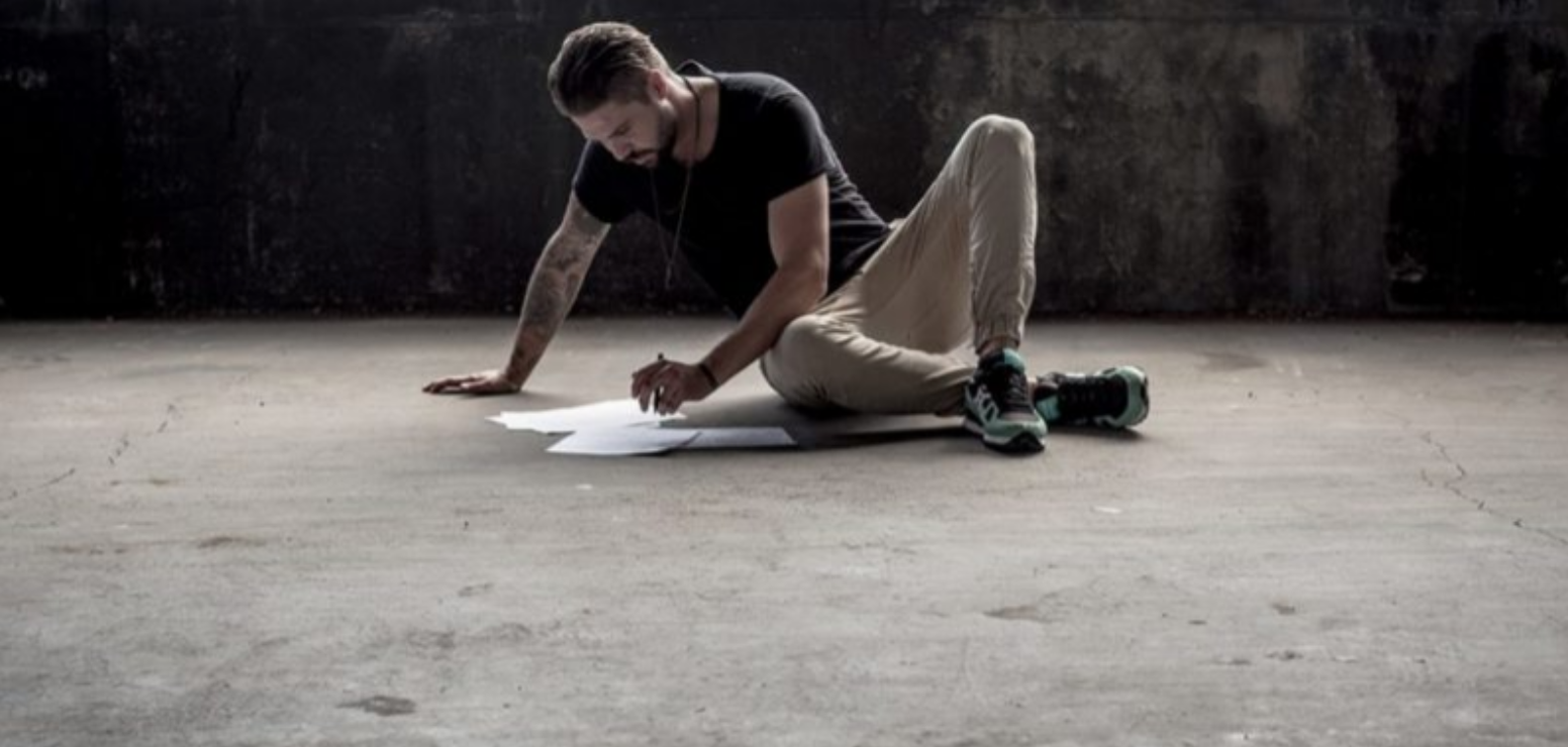 A man drawing alone on the floor