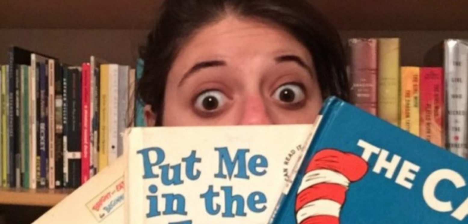A woman holding Dr. Seuss books with wide eyes.