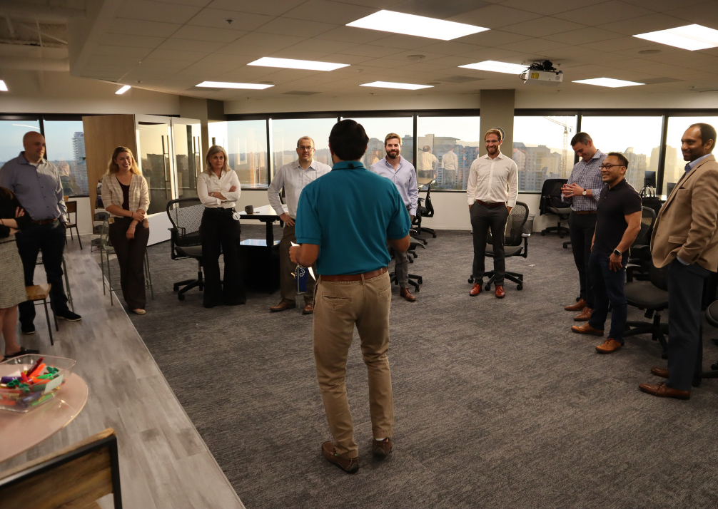 Akshay presenting in front of group of people in a bright, open office