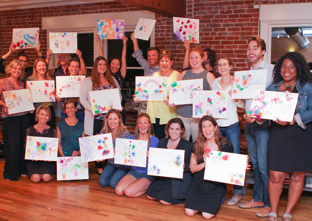 Group of people holding their artwork
