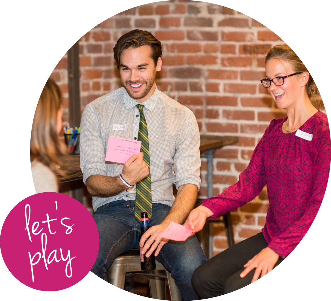 A man and woman sitting next to each other smiling. 'Let's Play' in a pink circle in the corner.