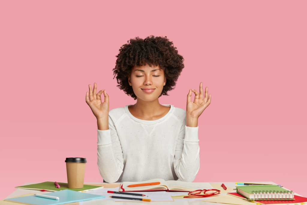 A young woman mediating at her desk